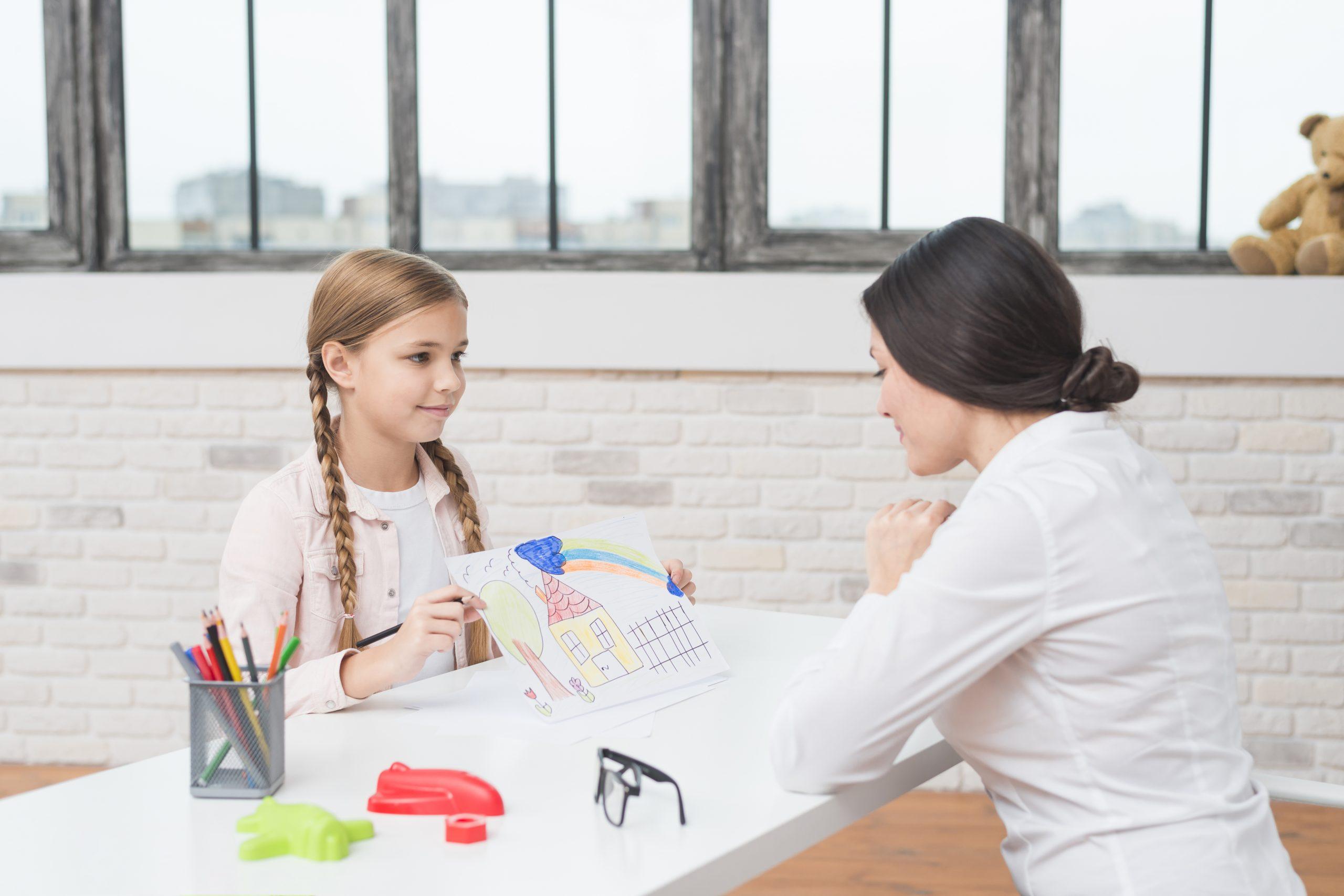 Dziecko pokazujące namalowany domek podczas terapii